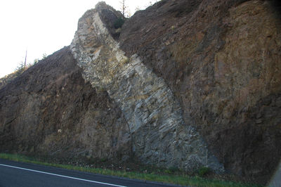Figure 2.28: An andesite dike intrudes through a volcanic debris flow conglomerate exposed by a roadcut in the Absaroka Range, Wyoming.