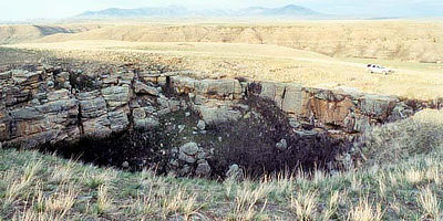 Figure 10.20: The Belt Meteor Crater southeast of Great Falls, Montana, is a sinkhole in the Madison Limestone measuring 10 meters (35 feet) deep and 30 meters (100 feet) across.