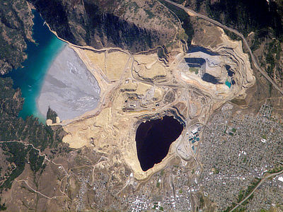Figure 5.11: The Berkeley Pit and associated tailings pond. This open pit copper mine reaches a depth of about 540 meters (1780 feet), and is filled to a depth of about 270 meters (900 feet) with metal-laden acidic water. The mine is 1.6 kilometers (1 mile) long and 0.8 kilometers (0.5 miles) wide.
