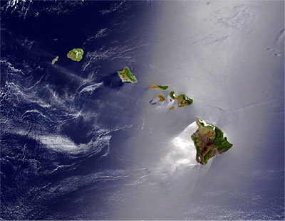 Figure 9.13: The effect of the northeast trade winds is seen in the shiny, highly reflective, calm water southwest of Hawai'i Island, where the ocean lies in the lee of the island's big volcanoes.