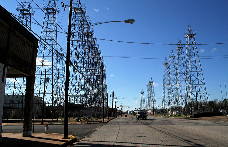 "Figure 7.14: Oil derricks line a street, once known as ""the world's richest acre,"" in downtown Kilgore, Texas. At the height of the Texas Oil Boom, more than 1100 oil wells operated within city limits."