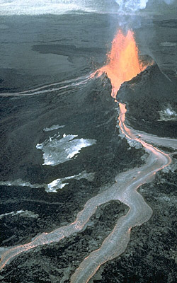 Figure 2.32: A flank eruption on Kīlauea. The vent erupts a fountain of lava that feeds a channelized lava flow. The dark color of the flow in the lower portion of the photo shows how quickly the surface of the molten lava freezes when in contact with air, while liquid lava continues to flow beneath the chilled crust.