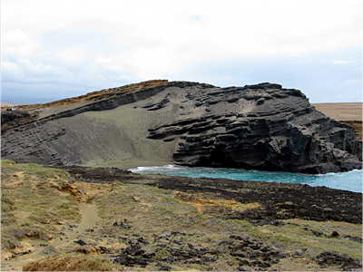 "Figure 4.26: Mahana littoral cone on Hawai'i Island, now breached by the ocean. The tephra here contains abundant olivine crystals that erode to form a ""green sand beach."""
