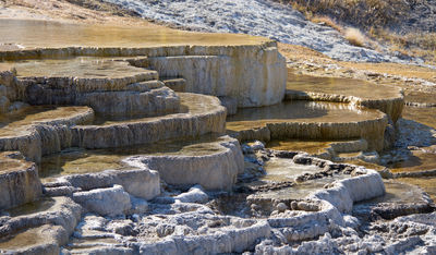 Figure 2.33: The travertine terraces of Mammoth Hot Springs in Yellowstone National Park precipitated over thousands of years as hot water from the spring cooled and deposited calcium carbonate. Over two tons of carbonate minerals in solution flow through the hot springs every day.