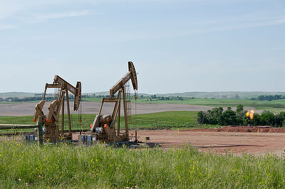 Figure 7.9: Oil pumpjacks in McKenzie County, North Dakota. The flame on the right-hand side is a flare that burns off natural gas separated from the oil.