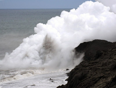Figure 4.25: At Kīlauea a lava tube empties into the ocean creating a jet of ash and steam. Repeated interaction of lava and seawater can form littoral cones.