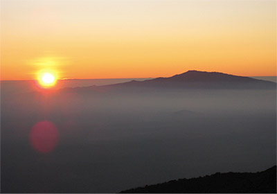 Figure 9.16: Trade wind inversion. The summit of Hualālai, at sunset, rises above the inversion layer while hazy and humid boundary layer air remains below. The Hualālai summit is 2521 meters (8271 feet), and here the inversion is ~1980 meters (~6500 feet).